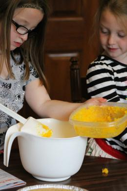 girl putting pumpkin into mix