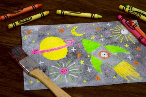 Let your kids create their own galaxy. With a box of crayons and some black watercolor paint, white paper is transformed into a stellar and imaginative piece of art.